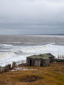 Dramatisch zeegezicht met een woeste witte zee en een vissershut aan de kust. kandalaksha baai. umba. rusland.