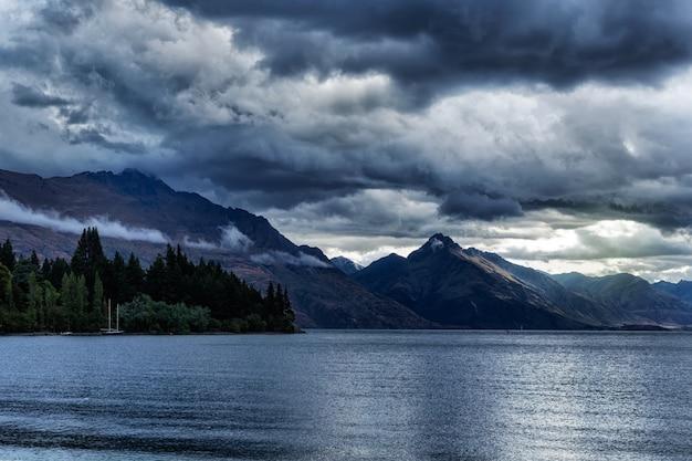 Dramatische avondlucht over de bergen en het meer wakatipu in nieuw-zeeland