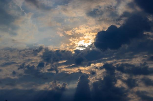 Dramatische blauwe hemel met donkere wolken en oranje zon