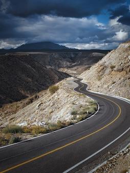 Dramatische cloudscape over lege weg door schilderachtige canyon in santa rosalia, baja california, mexico