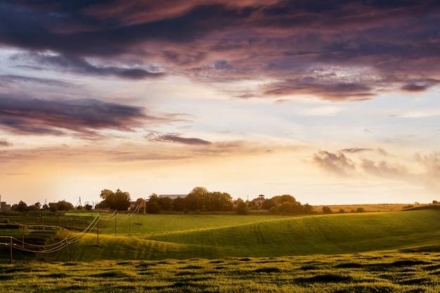 Dramatische hemel boven het veld tijdens de zonsondergang. landelijk landschap met donkere wolken