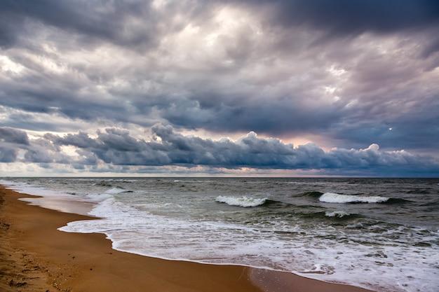 Dramatische hemel op een ochtendzeegezicht. zonsopgang op een zandig overzees strand.