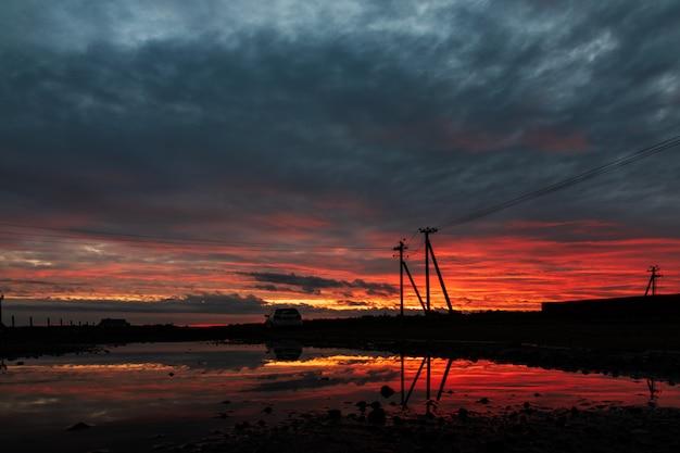 Dramatische hemel powerline in zonsondergang scène reflectie na regen