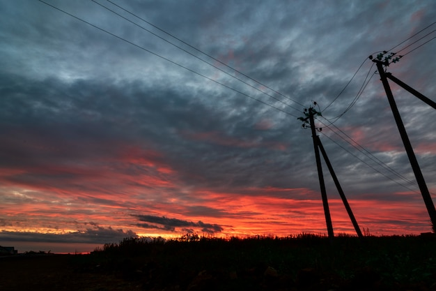 Dramatische hemel powerline in zonsondergang wolken scène reflectie na regen