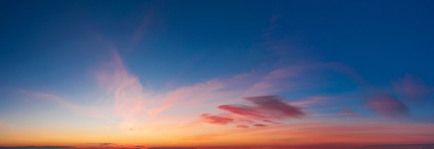 Dramatische kleurrijke hemel met zachte wolken bij zonsondergang.