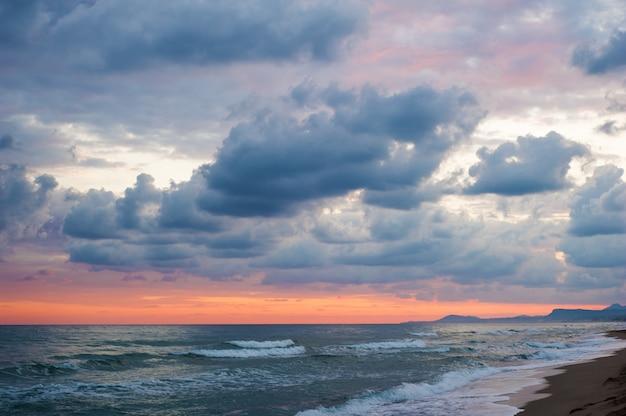 Dramatische kleurrijke wolken en zee
