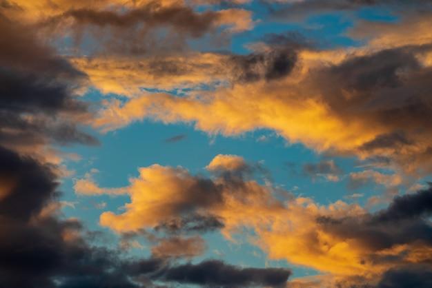 Dramatische pluizige wolk verlicht door verdwijnende stralen bij zonsondergang donkere onweerswolken over de blauwe lucht