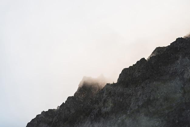 Dramatische sombere mist tussen gigantische rotsachtige bergen