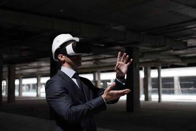 Dramatische taille-up portret van zakenman vr-uitrusting dragen op bouwplaats terwijl toekomstige project in 3d visualiseert,