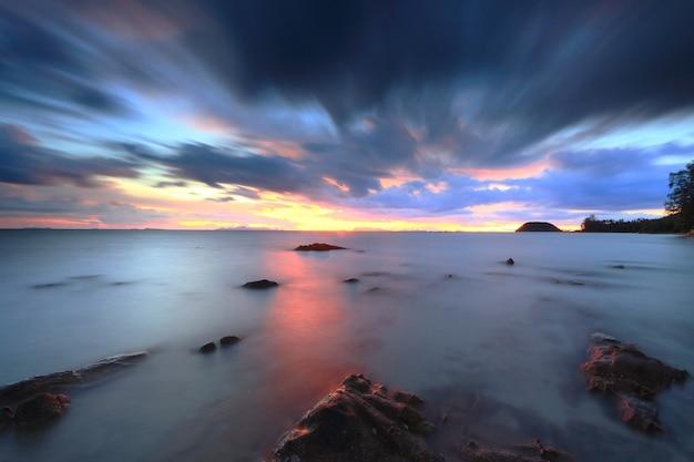 Dramatische tropische zonsonderganghemel en overzees bij schemer