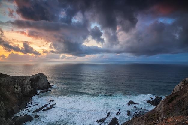 Dramatische zeegezicht van de zonsondergang, op de rotsen costa vicentina sagres