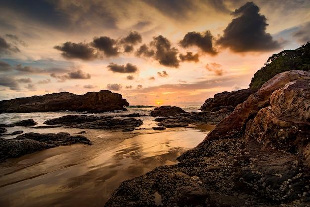 Dramatische zonsondergang hdr over overzees strand op zuideneilanden thailand met een natuurlijke rots.