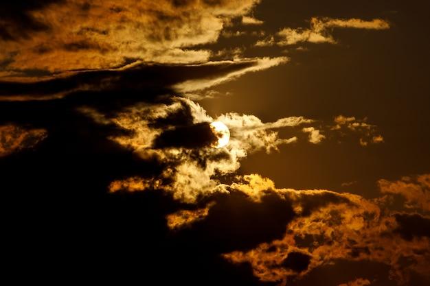 Dramatische zonsondergang met wolken. de ronde zon gaat zitten.