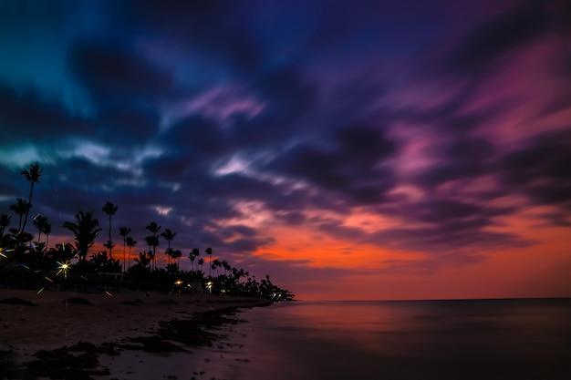 Dramatische zonsondergang over het exotische strand, met palmen.