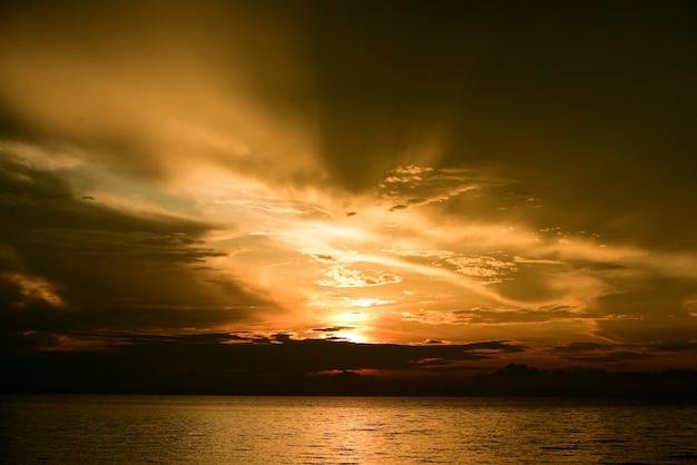 Dramatische zonsondergang wolken weerspiegeld op het water zee. tropisch landschap op gouden uur