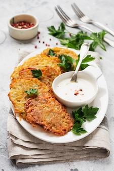 Draniki aardappelbeignets, vegetarische aardappelpannenkoekjes, geserveerd met verse kruiden en knoflookyoghurtsaus