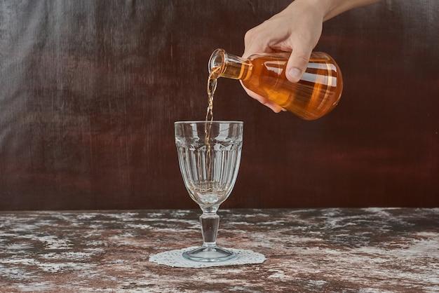 Drank in het glas zetten.