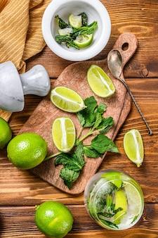 Drank maken van gereedschappen en ingrediënten voor cocktail, limonade, mojito. limoen, ijs en munt. houten achtergrond. bovenaanzicht.