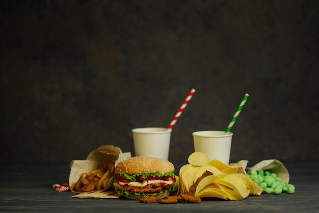 Drankjes in een kartonnen beker met een papieren tube en hamburger, zoute snacks, pretzels, chips.