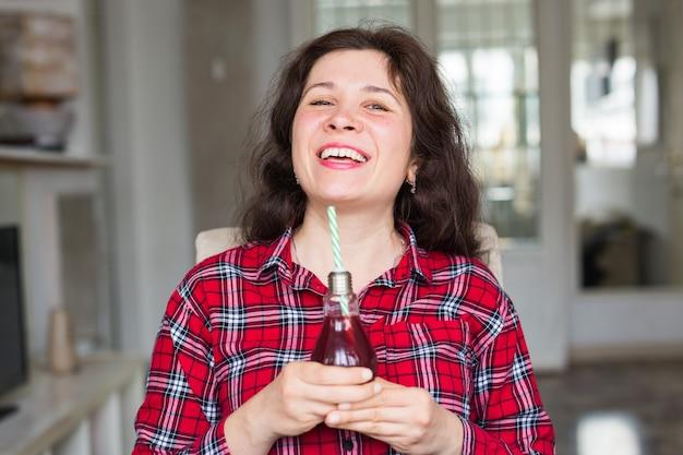 Drankjes, mensen en levensstijlconcept. close-up van gelukkige vrouw thuis drinken van cola met stro.