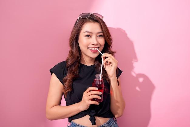 Drankjes, mensen en lifestyle concept - close-up van gelukkige vrouw thuis drinken cola met rietje