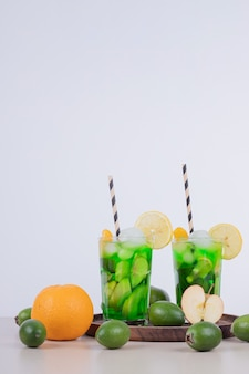 Drankjes met appel, feijoa en stro op wit