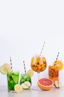 Drankjes met appel, grapefruit en stro op wit
