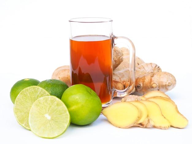 Drankkruidendrank met honing in glas en kruidenplak met verse gemberwortel en groene citroenenkalk.