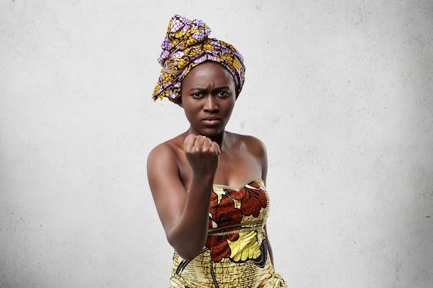 Dreigende zwarte vrouw met grote ogen en volle lippen dragen kleurrijke sjaal op hoofd en jurk met haar vuist op zoek boos en woedend dreigend met gebaar. emotionele vrouw met een donkere huid