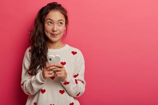 Dremay aangenaam uitziende tienermeisje met paardenstaart, draagt casual trui, maakt gebruik van mobiele telefoon