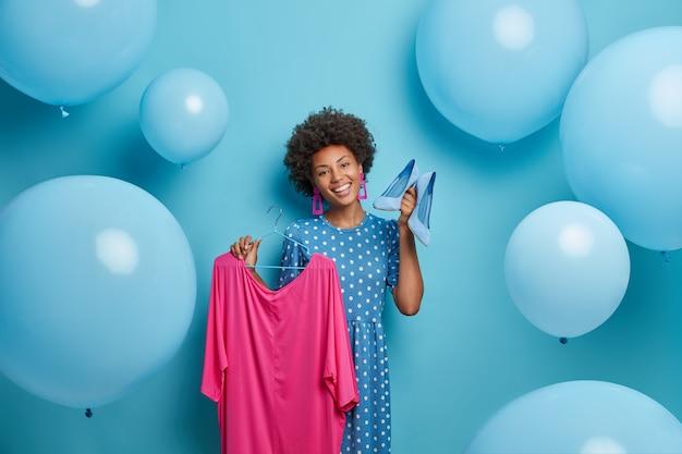 Dressing en kledingconcept. vrolijk lachende modieuze vrouw toont haar nieuwe aankopen, outfit kiest om te dragen, elegante roze jurk op hanger en blauwe schoenen met hoge hakken houdt, staat binnen