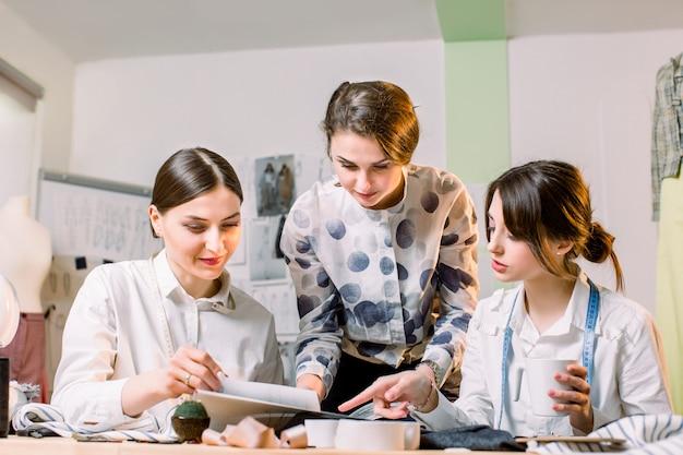 Drie aantrekkelijke jonge modeontwerpers die zorgvuldig nieuwe modieuze broekstijlen creëren. naaisters die kleding maken. mode, naaister, naaien concept
