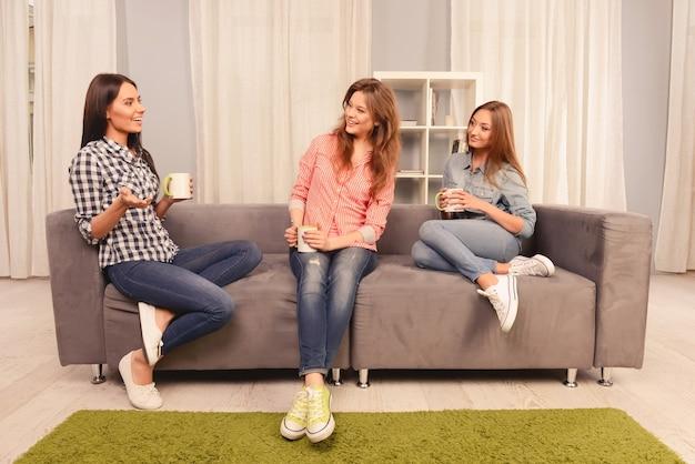 Drie aantrekkelijke meisjes die op bank met kopjes thee zitten en lachen
