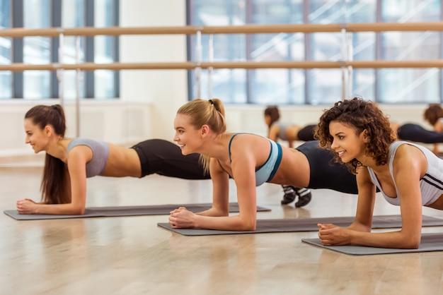 Drie aantrekkelijke sportmeisjes die terwijl het doen van plank glimlachen.