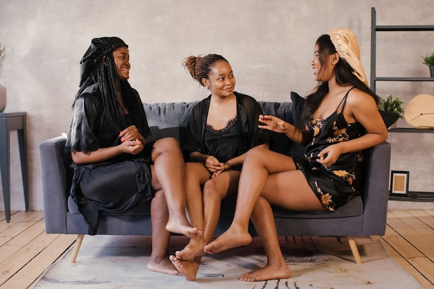 Drie afrikaanse amerikaanse meisjes die op de laag zitten roddelen, bespreken