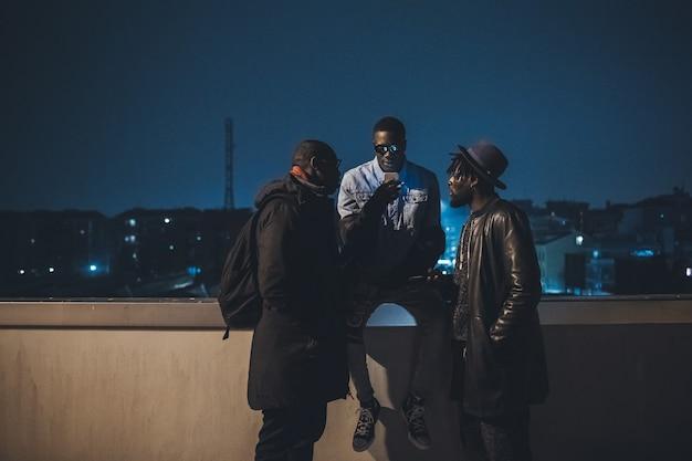 Drie afrikaanse vrienden buiten zitten en kijken naar de smartphone