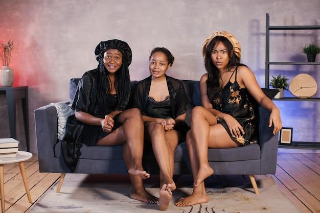 Drie afro-amerikaanse meisjes zittend op de bank tv kijken en lachen