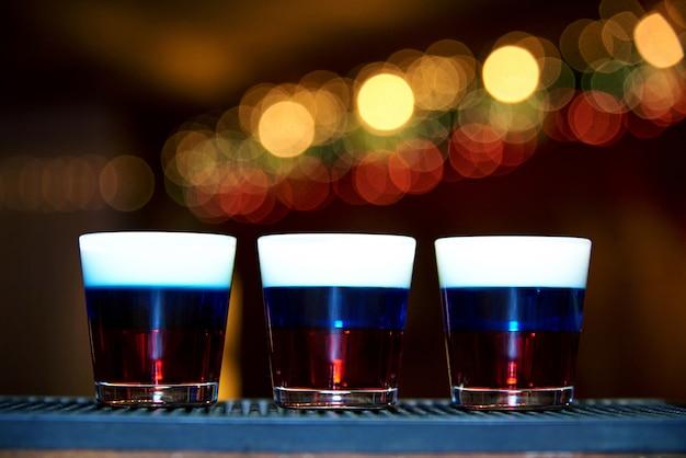 Drie alcoholische schoten op een donkere achtergrond met een bokeh