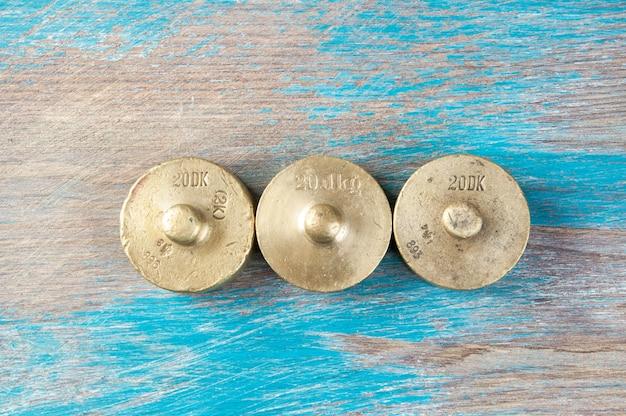 Drie antieke bronzen gewichten voor schalen op blauwe houten achtergrond. kopieer ruimte voor rekwisieten voor tekst en voedselfotografie.