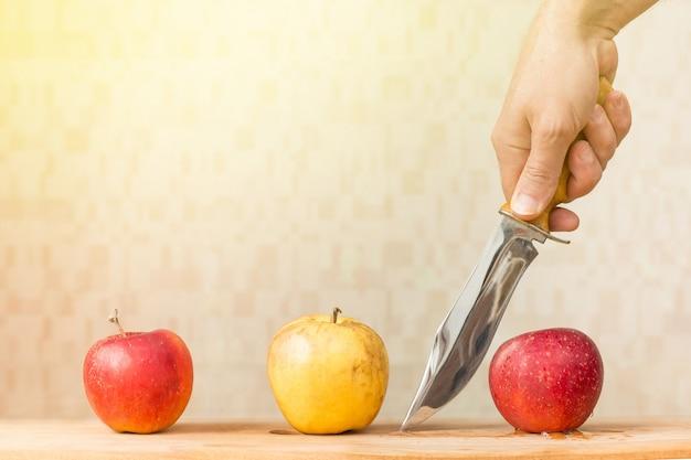 Drie appels en mes in de hand van de man