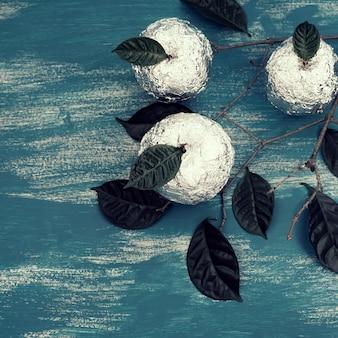 Drie appels ingepakt in folie zijn natuurlijke groene bladeren.