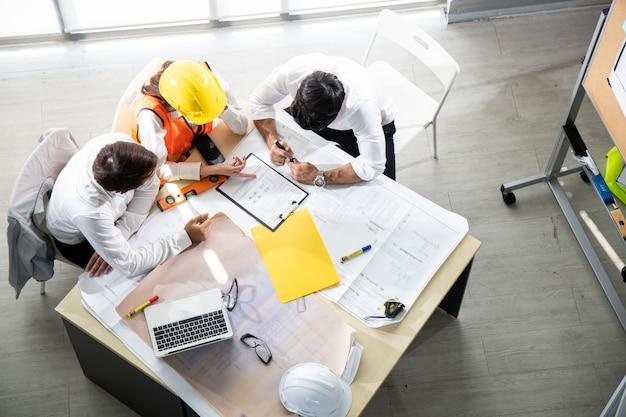 Drie architecten in het kantoor en bespreken ontwerpproject op tafel.