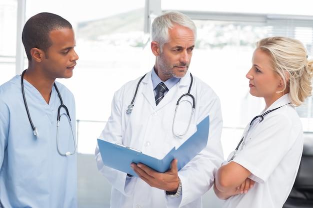 Drie artsen die een dossier onderzoeken