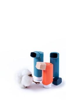 Drie astma-inhalatoren op een afgelegen witte achtergrond. medisch begrip.