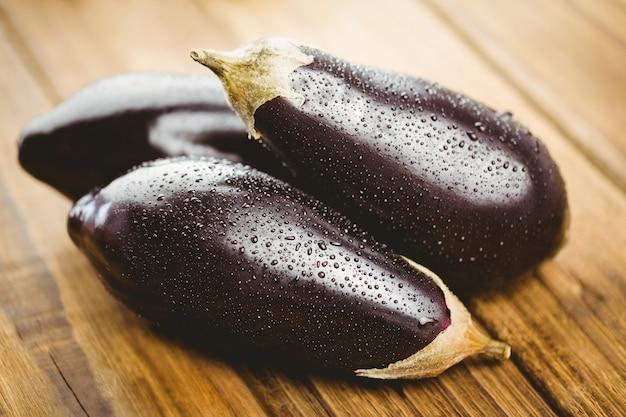 Drie aubergines op een houten bord