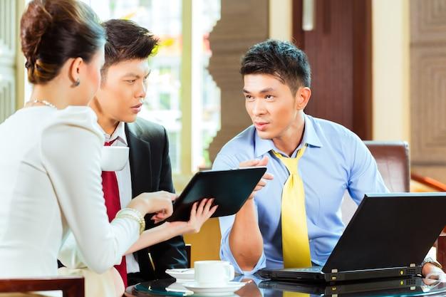 Drie aziatische chinese kantoormensen of zakenlieden en zakenvrouw met een zakelijke bijeenkomst in de lobby van een hotel bespreken documenten op een tabletcomputer terwijl het drinken van koffie