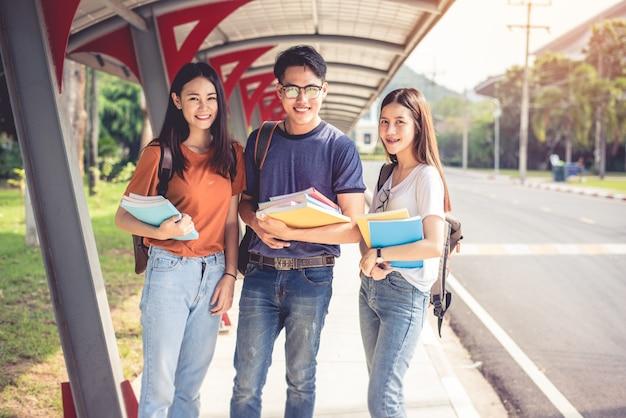 Drie aziatische jonge campusstudenten genieten samen van tutoring en boeken lezen