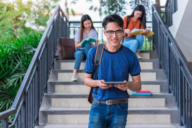 Drie aziatische jonge campusstudenten genieten van tutoring en het lezen van boeken samen bij trede