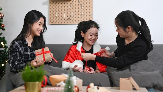 Drie aziatische kinderen die kerstcadeau openen en kerst samen thuis vieren.