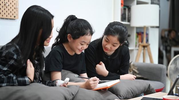 Drie aziatische kinderen die samen online studeren in de woonkamer.